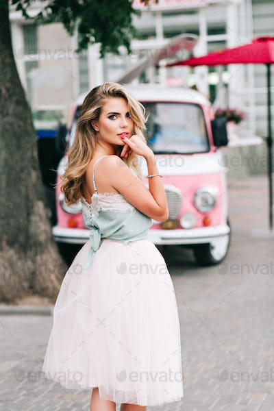 View from back pin up styled girl with long blonde hair on pink retro car background. She wears ligh