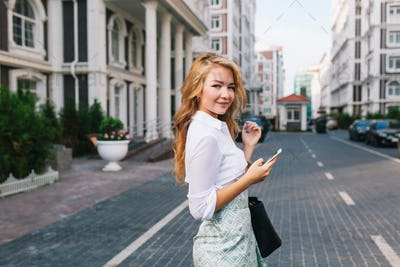 Pretty blonde business woman with long hair in white shirt walking on street around British quarter.
