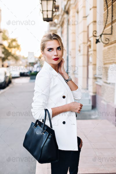 Portrait pretty woman in white jacket on street in city. She touching neck, looking to side