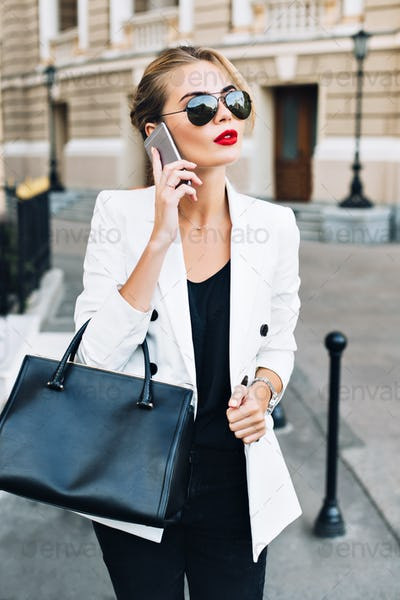 Portrait attractive woman in sunglasses with red lips walking on street . She wears white jacket, bl