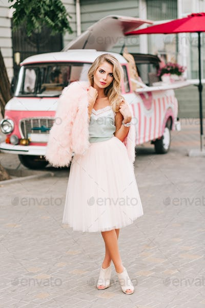Full-lenght pin up styled girl in tulle skirt with long blonde hair on retro car background. She hol
