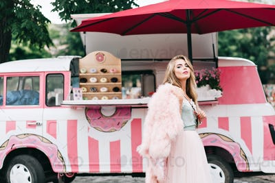 Beautiful girl with long blonde hair in tulle skirt on retro coffee car background. She wears pink f