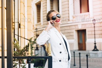 Portrait attractive woman in sunglasses on street. She speaking on phone and smiling to camera