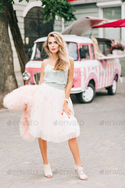 Full-lenght fashion model in light tulle skirt with long blonde hair on retro car background. She ho