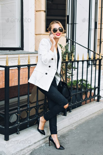 Attractive woman on heels is leaning on fence on street. She speaking on phone and smiling with red