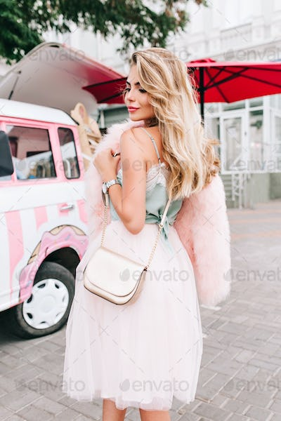 Vertical view from back pin up girl in tulle skirt on retro car background. She has long blonde hair