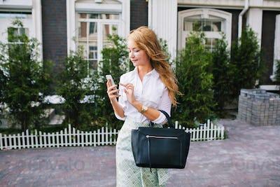 Stylish blonde girl with long hair in white shirt walking around British quarter. She using phone, l