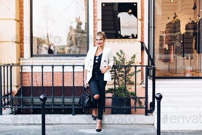 Attractive model in white jacket on heels is leaning on fence on shop background. She keeps hand in