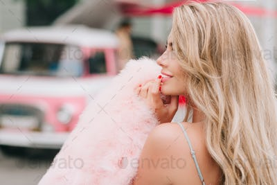 Closeup portrait from back pin up styled girl holding pink fur stole on retro car background. She ha