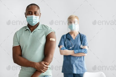 Mature lady nurse or doctor in uniform, protective mask stands with millennial african american