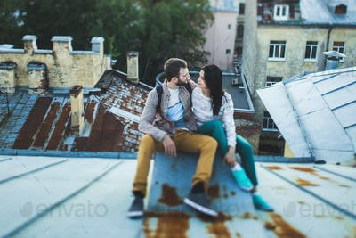 Young happy couple sitting on the roof in St. Petersburg. Beautiful view of the city from above