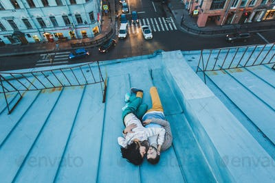Young hipster couple lying on the roof and kissing. Beautiful view of the city from above.