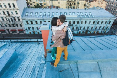 Young happy couple walking on the roofs of St. Petersburg. Beautiful view of the city from above