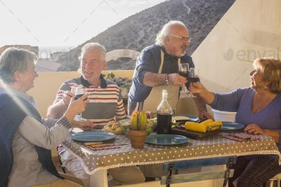 Happy cheerful group of senior aged old people enjoy together toasting and eating in friendship