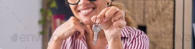 Focus on bunch of keys from house flat apartment in hand of smiling female. Blurred portrait
