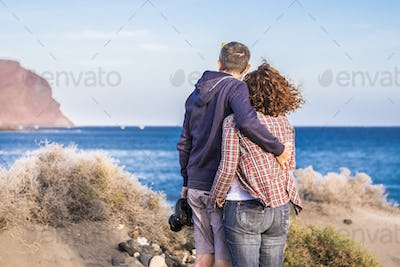 Adult caucasian couple viewed from back hug with love enjoying and looking the ocean on vacation