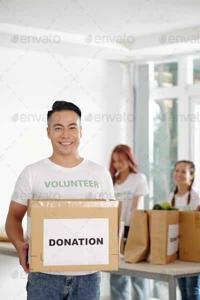 Volunteer holding cardboard box