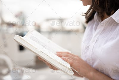 Female hands holding a book close up.