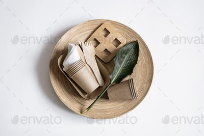 Composition with a set of disposable paper dishes and a ceramic plate top view.