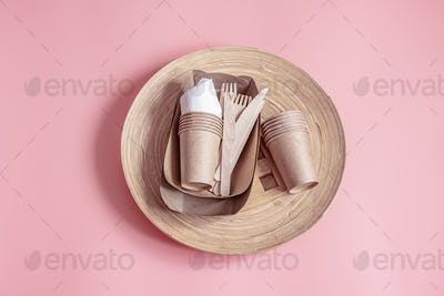 Composition with disposable paper and bamboo dishes close up.