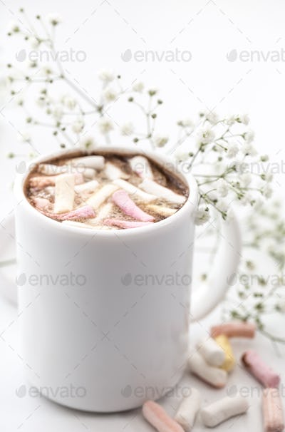 white coffee Cup with marshmallows and flowers