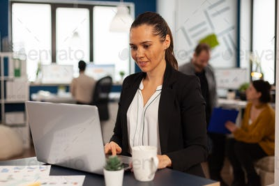 Enthusiastic woman manager browsing on internet using laptop