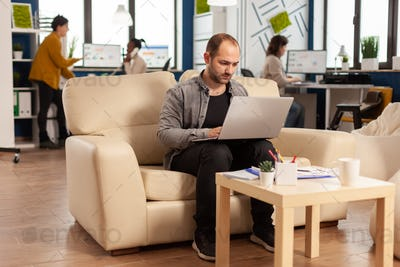 Businessman strart up modern office typing on laptop sitting on couch
