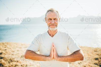 Close up portrait senior man doing yoga exercises at the mountain on the background.