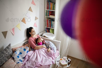 Tired mother looking after sick small daughter in bed at home, coronavirus concept.