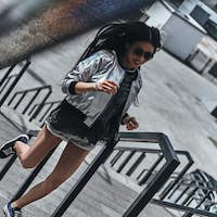 On the move. Beautiful young woman in casual wear running up the stairs outdoors