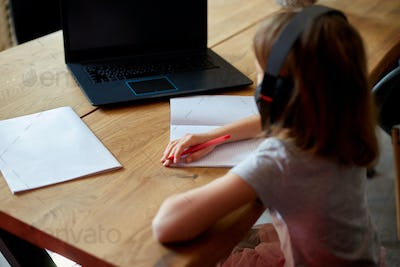 Cute little girl with headphones using laptop to study at home