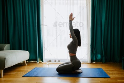Young attractive woman practicing yoga at home. stretching practice