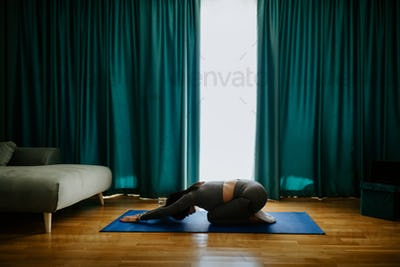 Young woman practicing yoga at home. Posture practicing
