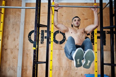 Fit and muscular arabian man doing workouts in gym.