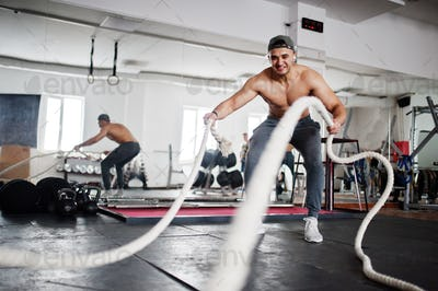 Fit and muscular arabian man working out with heavy ropes in gym.