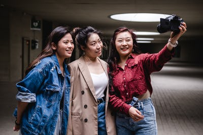Asian female friends bloggers creating content for social media while making a video with a camera.
