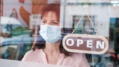 Woman with face mask changing closed to open sign on window looking outside