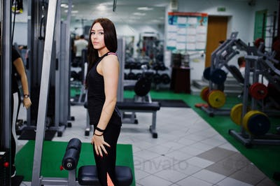 Young sport girl workout in gym. Fitness woman doing exercises.