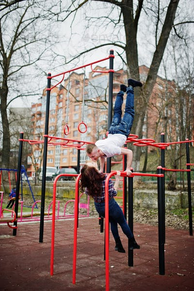 Stylish couple wear on checkered shirt in love together kissing on bars workout.