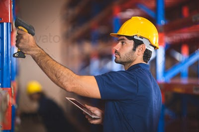 Worker with scanner making review of goods in warehouse storage, logistic industry concept