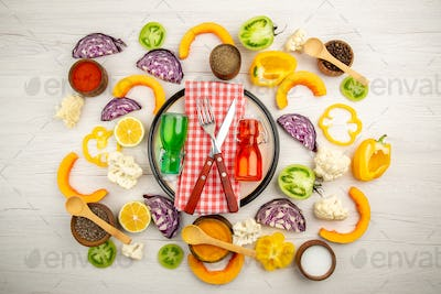 top view crossed fork and knife on napkin green and red bottles on white platter cut vegetables