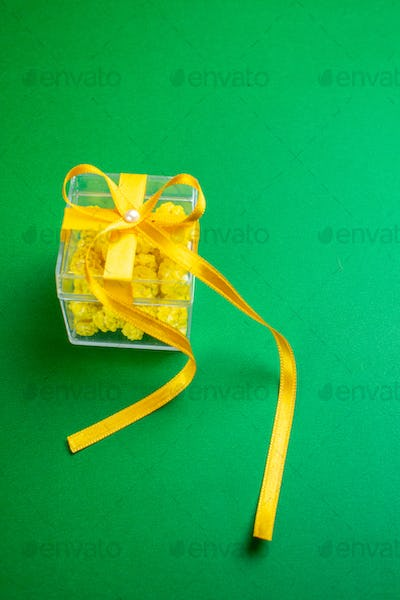 Side view of Christmas beautiful yellow gift box with candies on green background