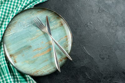 top view crossed knife and fork on round platter green and white tablecloth on black table free