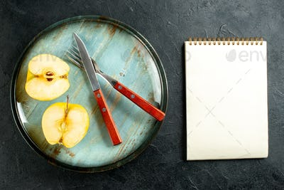 top view apples cut in half crossed fork and knife on round platter notepad on black background