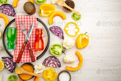 top view crossed fork and knife on napkin green and red bottles on white plate cut vegetables on