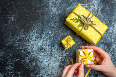 Top view of hand opening a small gift box and other two Christmas gift boxes on dark background