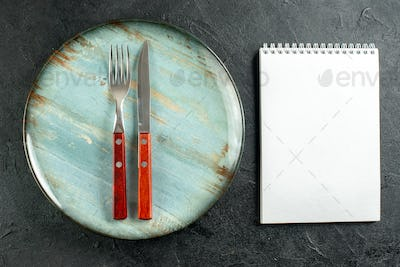 top view vertical fork and knife on round plate notebook on dark ground stock photo