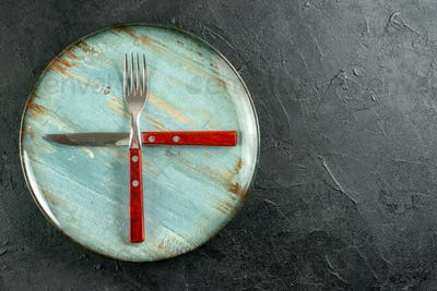 top view crossed fork and knife on round plate on dark ground copy place stock photo