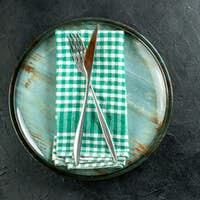top view crossed steel dinner knife and fork on green and white checkered napkin on platter on