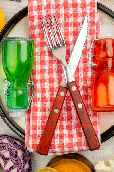 top view crossed fork and knife on napkin green and red bottles on white plate on table